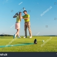 stock-photo-full-length-of-a-skilled-golf-instructor-teaching-a-young-woman-to-swing-the-driver-club-for-a-1116629534