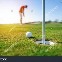 stock-photo-golfer-putting-golf-ball-on-the-green-golf-lens-flare-on-sun-set-evening-time-professional-golf-1722156607